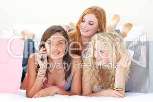 Happy teen girls after shopping clothes talking on mobile phone