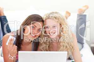 Portrait of teen girls shopping online in a bedroom