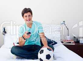 Teen guy watching a football match in television