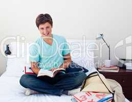 Smiling teenager studying maths in his bedroom