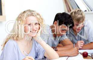 Smiling teen girl studying in the library with her friends