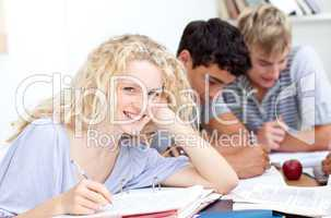 Happy teen girl studying in the library with her friends