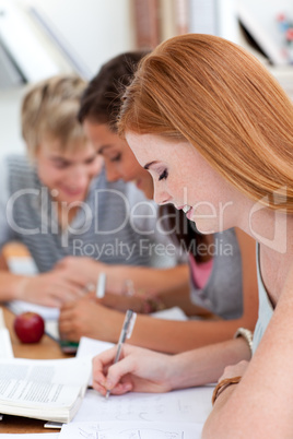 Teen girl studying in the library with her friends