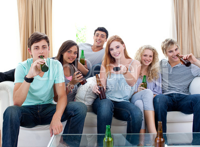 Friends drinking beer at home and watching tv