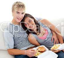 Teen couple eating burgers and fries at home