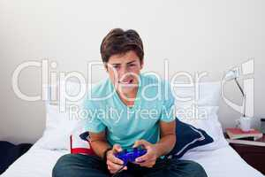 Teenager playing video games in his bedroom