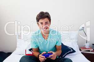 Happy teenager playing video games in his bedroom