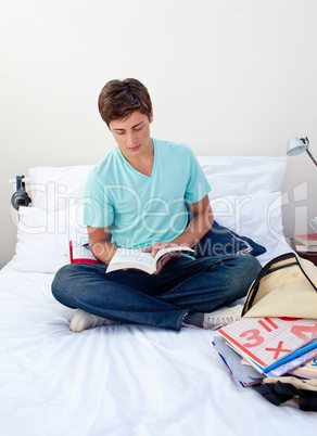 Teenager reading a book in his bedroom
