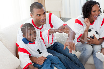 Excited Afro-American family wathing a football match