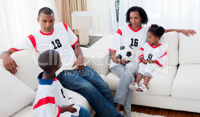 Afro-american family watching a football match