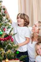 Mother and her children decorating a Christmas tree