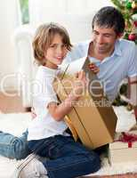 Happy Father and his son opening Christmas gifts
