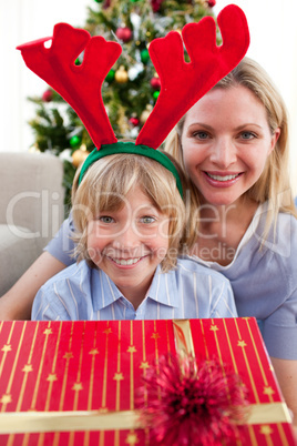 Happy mother and her son unpacking Christmas gift