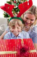 Smiling mother and her son opening Christmas present