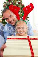 Portrait of a smiling father and his daughter opening Christmas