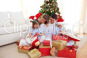 Portrait of a happy family opening Christmas gifts