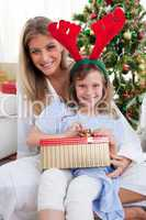 Smiling mother and her daughter unpacking Christmas gifts