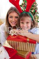 Portrait of a mother and her daughter holding Christmas presents