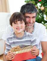 Father and son holding a Christmas gift