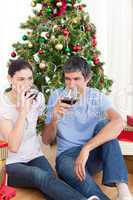 Couple drinking wine at homa at Christmas time