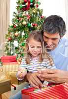 Dad and little girl playing with Christmas presents
