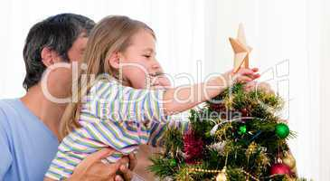 Little girl placing a star in a Christmas tree