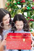 Mother and daughter playing with Christmas gifts