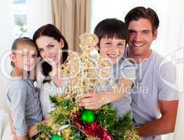 Portrait of a family decorating a Christmas tree