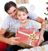 Happy little girl with her father receiving a Christmas present