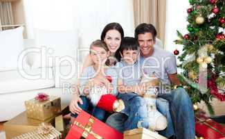 Happy family at Christmas time holding lots of presents