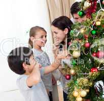 Smiling family decorating a Christmas tree with boubles