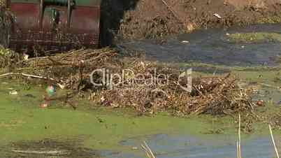 Removing silt and overgrown vegetation from a canal