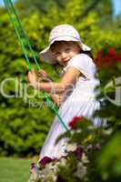a closeup portrait of a young girl on a swing