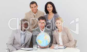 Multi-ethnic business team holding a terrestrial globe