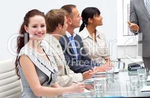 Smiling businesswoman listening to his colleague giving a presen