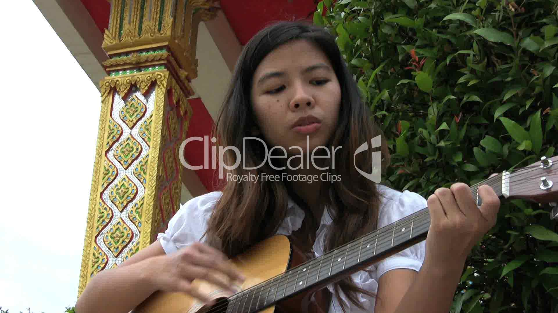 asian girl sings and plays worship songs royalty free
