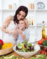 Litlle girl and her mother preparing a salad