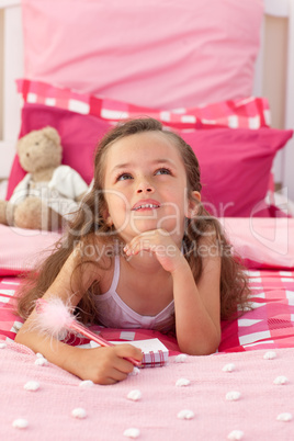 Portrait of a little girl lying on bed