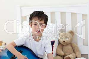 Little boy singing and playing guitar