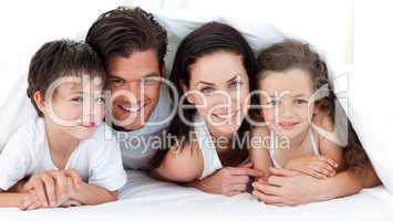 Portrait of a smiling family lying on bed