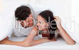 Couple talking together and lying on bed