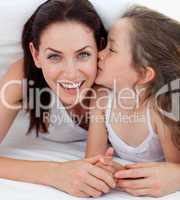 Little girl kissing her mother lying on bed