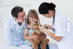 Smiling patient examining a teddy bear with a doctor