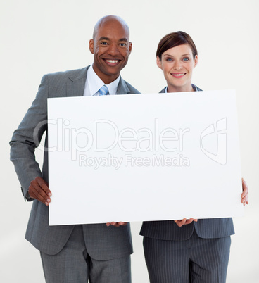 Smiling business people holding white card