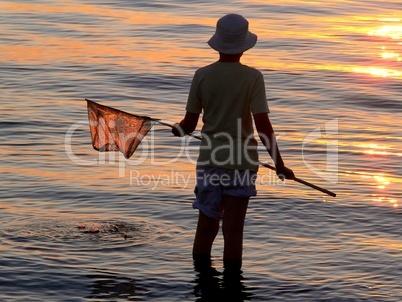 Kind mit Fischernetz vor Sonnenuntergang am Wasser