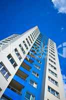 Hochhaus mit Fenstern und Balkon vor blauem Himmel