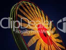 Langzeitaufnahme eines beleuchteten Riesenrads oder Karussell