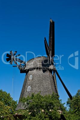 Nostalgische Mühle umrahmt von Bäumen unter blauem Himmel