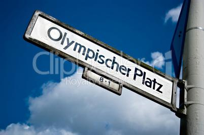 Straßenschild Olympischer Platz vor blauem Himmel im Sonnenlicht