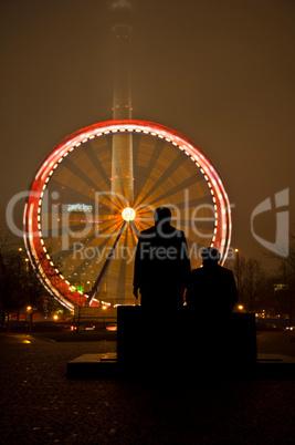 Marx und Engels Statuen am Alexanderplatz in Berlin mit Karussell im Hintergrund